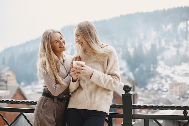 Ragazze in abiti leggeri. caffè invernale sul balcone. donne felici insieme.