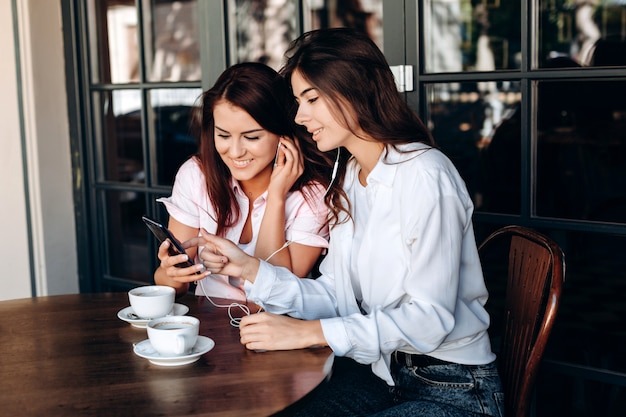 Girls listening to music sitting in cafe