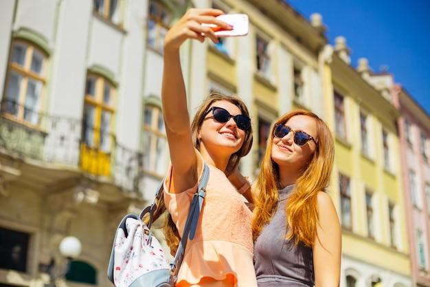 Девушки смотрят в камеру телефона и фотографируют себя на фоне города