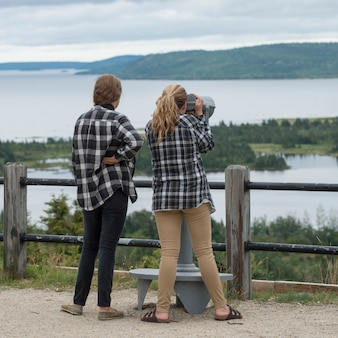Girls looking at bay view through a coin-operated binoculars, joey's lookout, gambo, newfoundland an