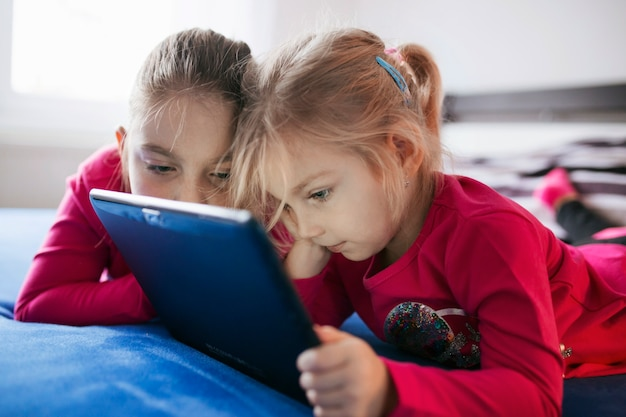 Girls looking at tablet on bed