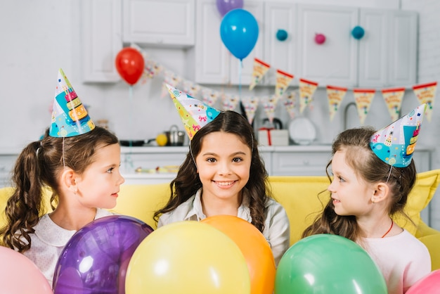Girls looking at their happy friend with colorful balloons