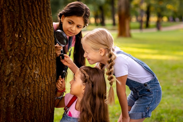 Girls looking at the tree stalk through the magnifying glass