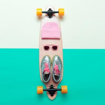 Девушки любят скейтборд. установите скейтбордиста. стильная активная жизнь. кроссовки, солнцезащитные очки, скейтборд, шапка pink vibration