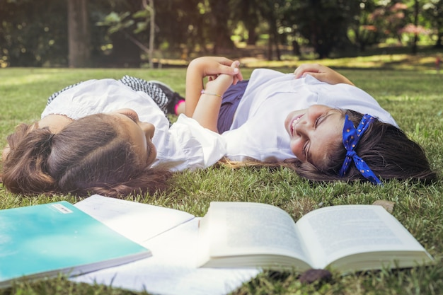 Girls lying on grass holding hands smiling