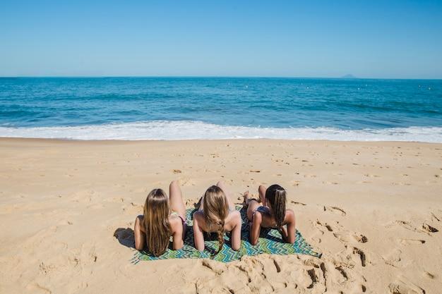 Girls lying on the sand