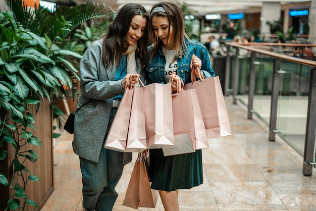 Girls make purchases in a shopping center, go shopping.