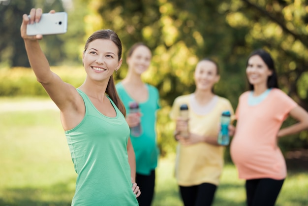 Girls make selfie with smiling pregnant on smartphone.