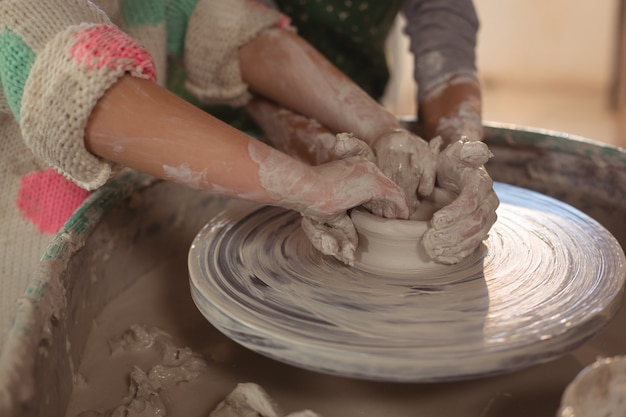 Girls making pot in pottery workshop