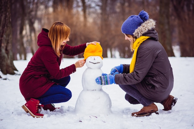 Girls molding a snowman