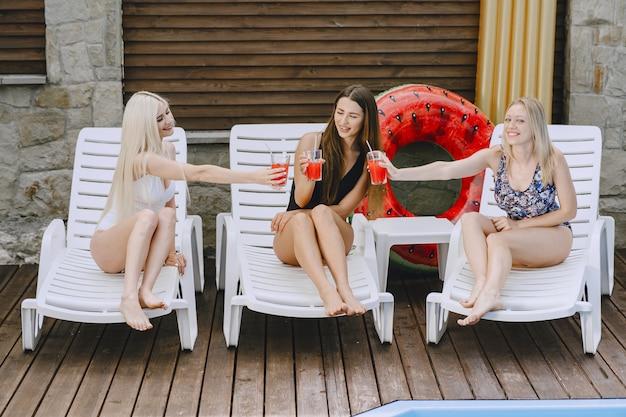 Девушки у бассейна. друзья в стильных купальниках. дамы на летних каникулах.