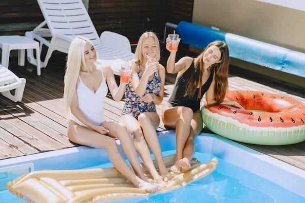 Девушки у бассейна. женщины в стильных купальниках. дамы на летних каникулах.