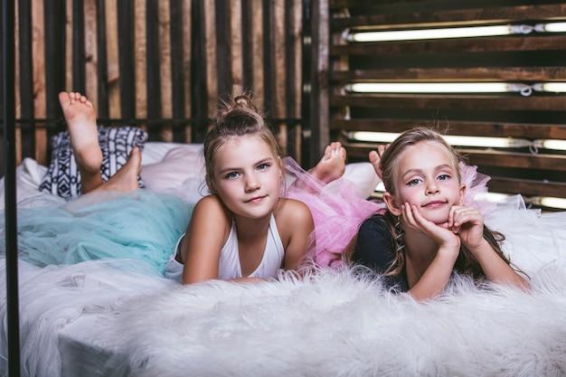 침실의 요정처럼 얇은 명주 그물 치마를 입은 침대 위의 소녀들