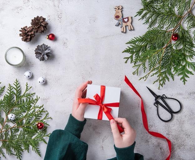 밝은 회색 테이블에 빨간 리본으로 화이트 크리스마스 선물을 여는 여자. thuja 트리, 촛불 콘 및 크리스마스 장난감 크리스마스 배경