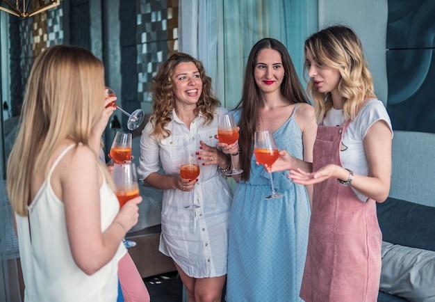 Девичья вечеринка. друзья красивые женщины с удовольствием на девичнике. они празднуют и пьют шампанское на девичнике. они говорят
