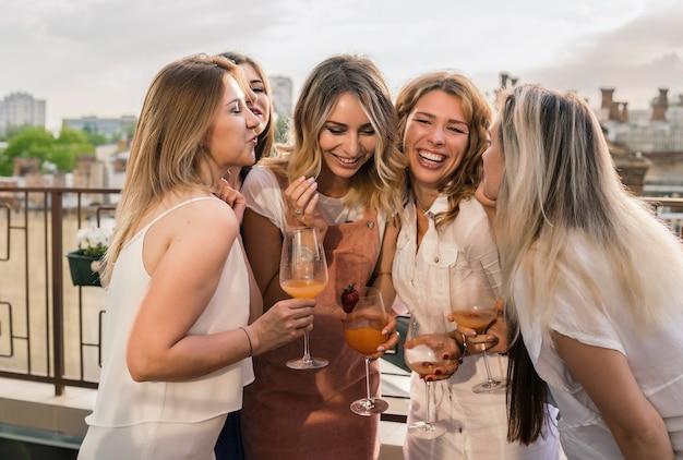 걸스 파티. 독신 파티에서 재미 발코니에 아름 다운 여자 친구. 그들은 암탉 파티에서 축하하고 샴페인을 마시고 있습니다. 건배