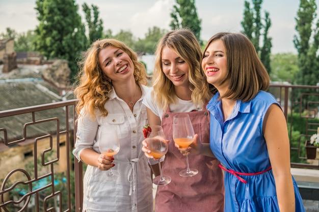 Девичья вечеринка. красивые подруги на балконе развлекаются на девичнике