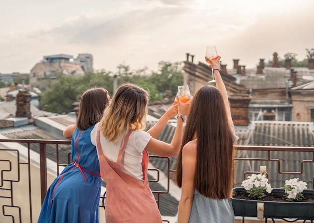 Девичья вечеринка. женщины стоят на балконе и смотрят, пьют шампанское