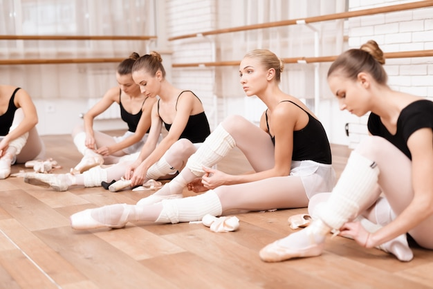 Girls perform stretching in the ballet hall.
