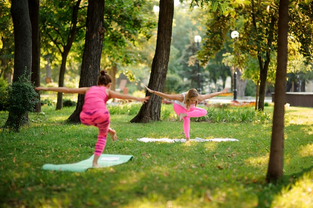 Girls in the pink sportsuits practicing yoga in the park