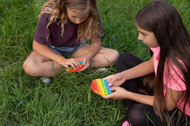 Girls play colorful silicone touch popular pop-it toy outdoors on green grass