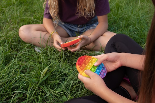 Girls play colorful silicone touch popular popit toy outdoors on green grass