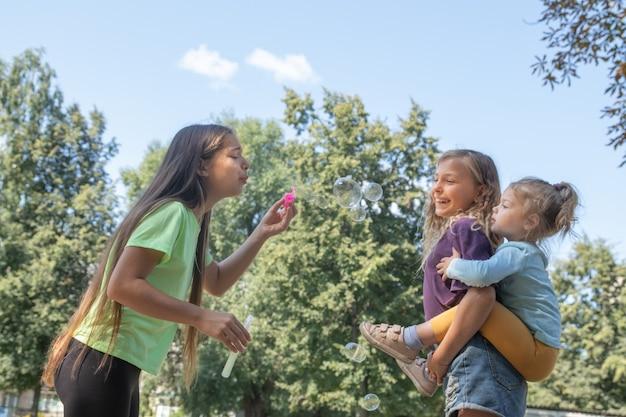 Девочки играют на улице с мыльными пузырями. концепция детства и веселья
