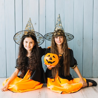 Girls in pointy hats sitting on floor with halloween bucket
