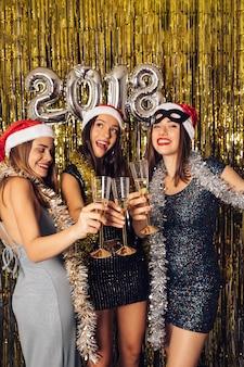 Ragazze in posa con champagne sul partito di nuovo anno