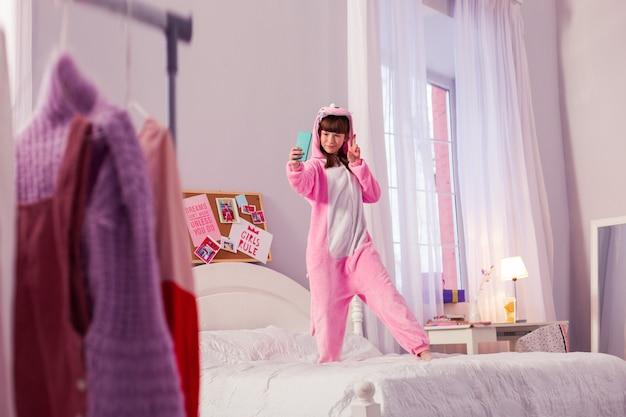 女の子パワー。ベッドの上に立って、電話で写真を撮るかわいい女の子