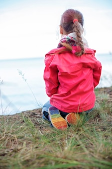 Girls power and tolerance. pretty girl in pink jacket and shoes with rainbow color bottom, sitting on the bank of sea and looking beyond horizon, focus on the colorful part of shoes
