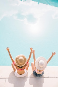 Girls raising arms in front of pool
