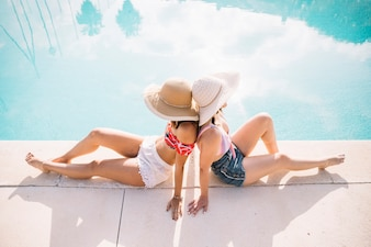 Girls relaxing in front of pool