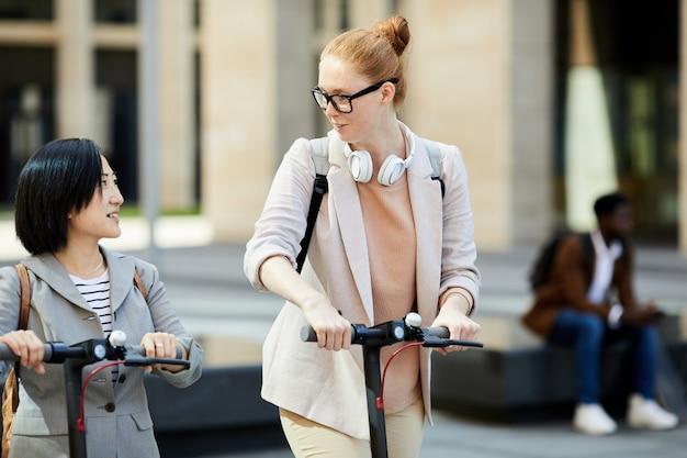 Девочки едут на скутерах в городе