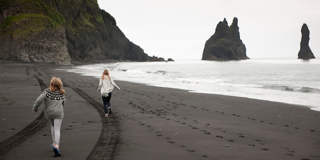 Girls running on black volcanic sand beach with tire tracks and footprints, cliffs