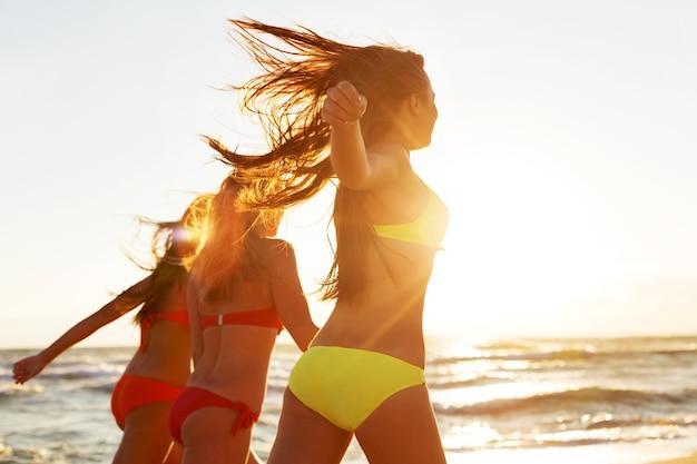 Девушки, бегущие на пляже, вечеринка на золотом фоне летнего заката