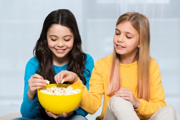 Girls sharing popcorn