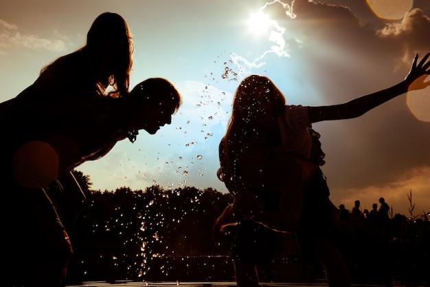 Силуэты девушек, играющих в воде против солнца