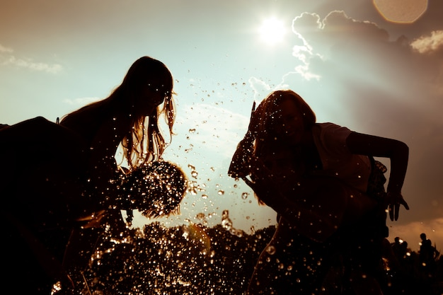 Girls' silhouettes playing in the water against the sun