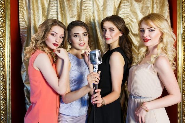 The girls sing karaoke in the restaurant.
