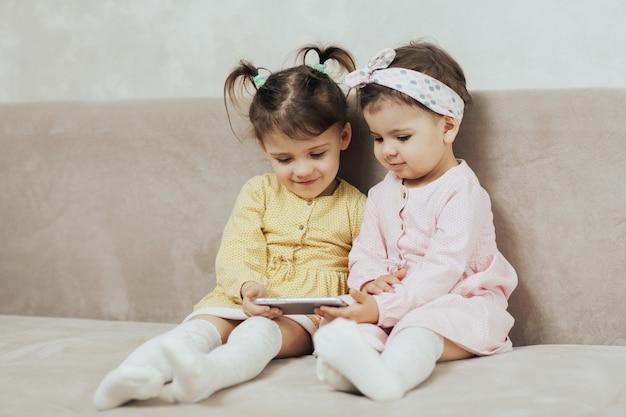 Девочки сестры сидят на диване в гостиной и смотрят мультики на смартфоне