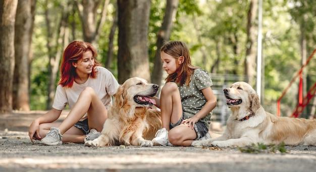 公園に座っているゴールデンレトリバー犬と女の子の姉妹。屋外で犬のペットと家族