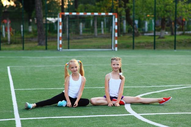 女の子はスポーツフィールドのより糸に座っています。