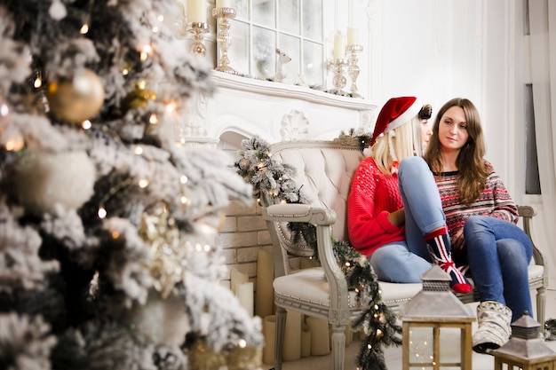 크리스마스 트리 옆에 집에 앉아있는 여자
