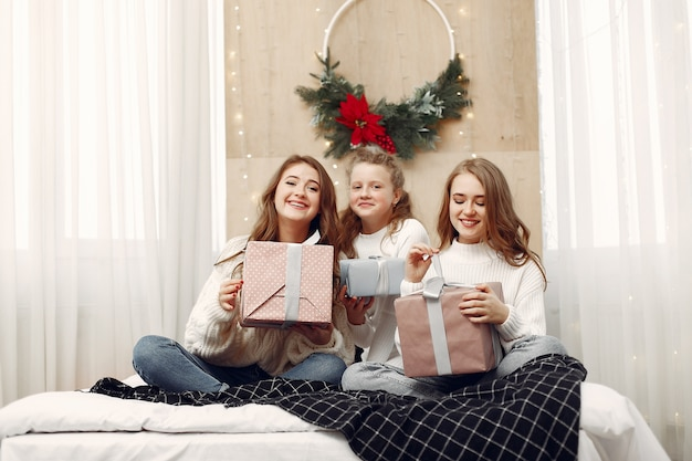 Girls sitting on the bed. women with gift boxes. friends preparing for christmas.