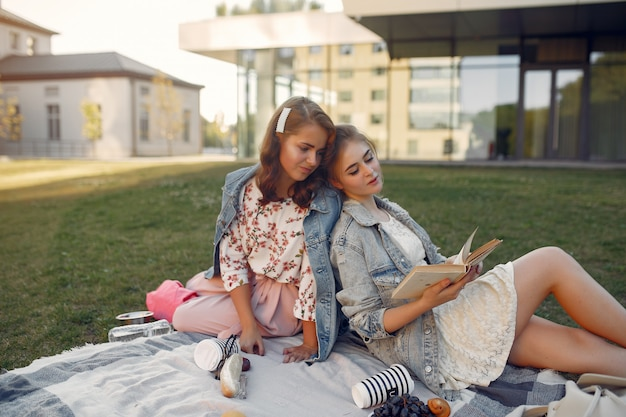 Girls sitting on a blanket in a summer park