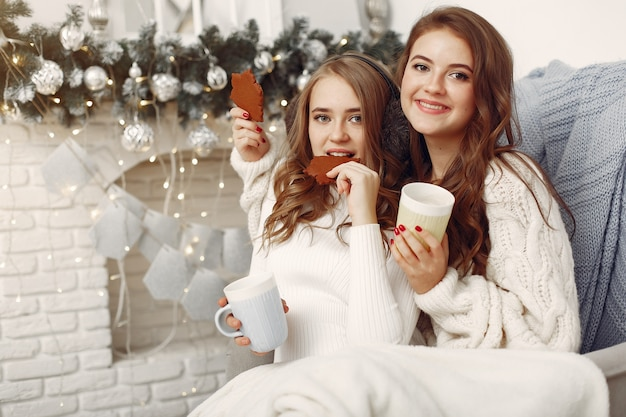 Girls sitting on the chair .women with cups. sisters preparing for christmas