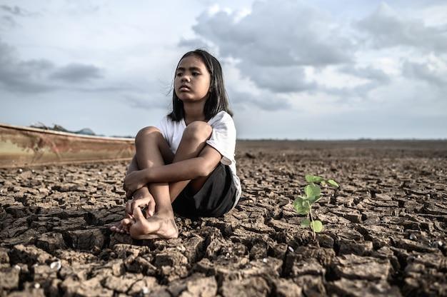 소녀는 무릎을 껴안고 하늘을보고 마른 땅에 나무를 가지고 앉아 있습니다.