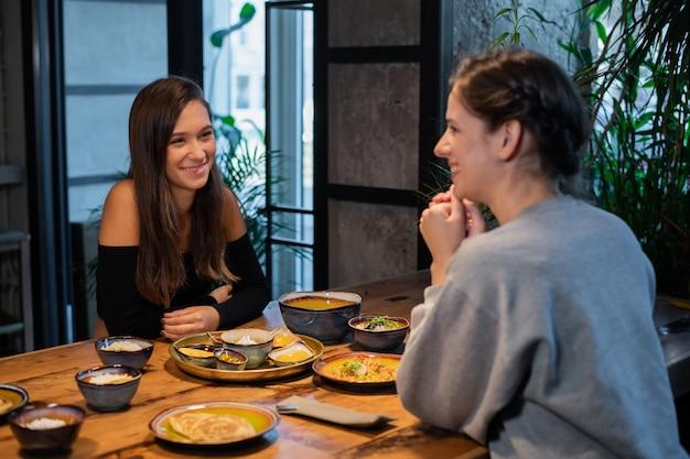 カフェに座ってフレンドリーな話している女の子