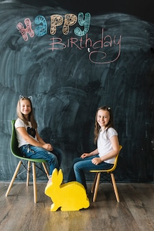 Girls sitting near happy birthday writing